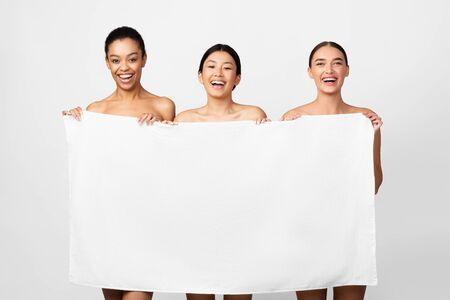 Three Multiethnic Women Holding Bath Towel Hiding Beautiful Naked Bodies Posing Over White Background. Studio Shot