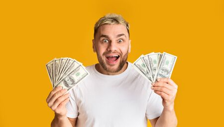 Joyful guy holds a lot of money in his hands on yellow background, empty space