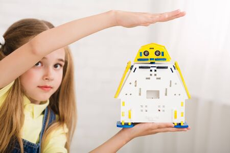Robotics concept. Schoolgirl showing her electronic toy, holding it on hand
