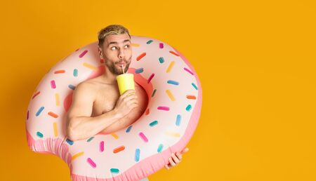 Ridiculous guy in inflatable ring, drinking cocktail from straw, empty space