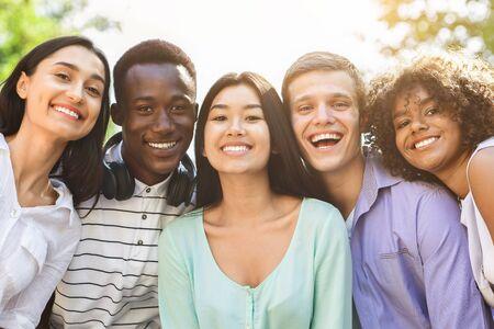 Porträt von fröhlichen interracial Teenager-Freunden, die draußen vor der Kamera posieren, lächeln und lachen, genießen, Zeit zusammen zu verbringen, Nahaufnahme Standard-Bild