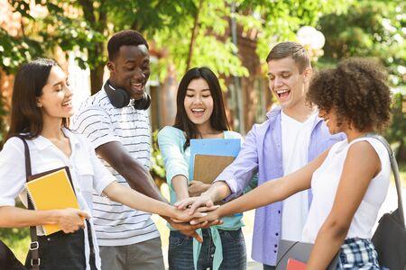 Concept d'éducation et d'unité. Groupe d'étudiants internationaux empilant les mains ensemble à l'extérieur sur le campus universitaire, célébrant le succès