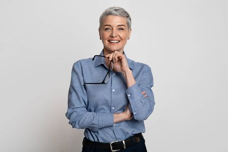 Portrait Of Beautiful Mature Businesswoman Holding Glasses And Smiling At Camera While Posing On Light Background In Studio, Free Space