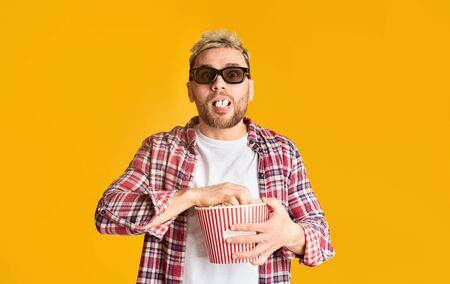 Excited man in 3d glasses filled his mouth popcorn on yellow background