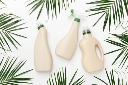 Bio Design of plastic bottles packaging of laundry and cleaning detergent among natural green leaves on white background
