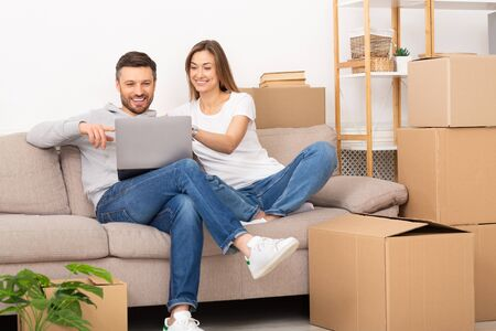 Young couple sit in new apartment with laptop, discuss home repair project in living room with sofa and stack of boxes. Moving and relocation concept.