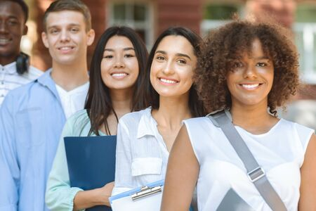 Modern Student Community. Closeup Portrait Of Multi-Ethnical Teens Posing Outdoors Against University Building Background
