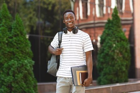 Happy smiling african american student guy with backpack and workbooks over university background, looking at camera and smiling