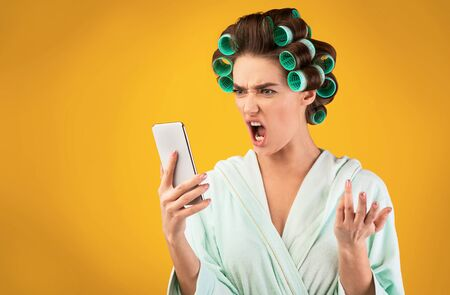 Angry Housewife Shouting At Cellphone Talking With Husband Standing On Yellow Studio Background. Copy Space Archivio Fotografico