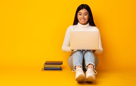 Students Lifestyle. Asian Girl Using Laptop Studying Sitting With Books On Floor In Studio On Yellow Background. Copy Space