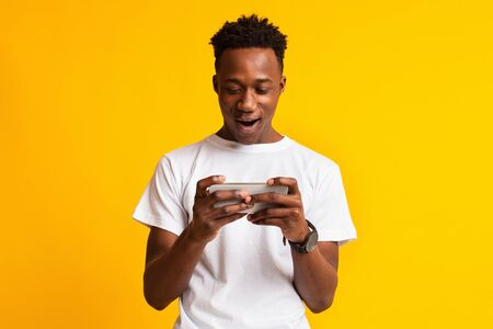 Online games. Excited african guy holding cellphone and playing video games, yellow studio background