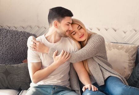 Young man and woman embracing on sofa in living room