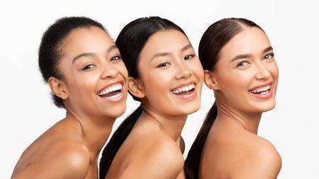 Three Multi-ethnic Women Posing Smiling To Camera Standing Over White Background. Studio Shot, Panorama