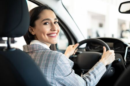 Buying New Car. Happy Young Woman Testing Automobile Sitting In Auto In Dealership Center. Selective Focus