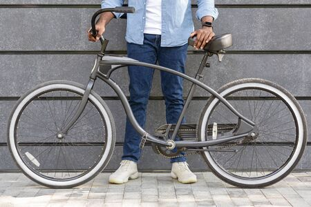 Unrecognizable Afro Man Holding Bicycle With Stylish Design, Standing Over Grey Urban Wall, Cropped Image, Closeup