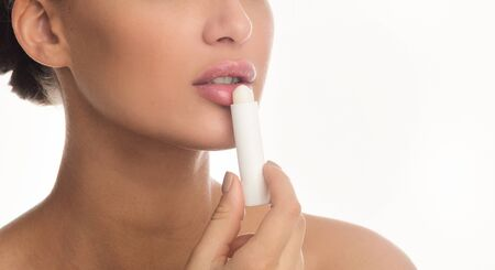 Nude Makeup Concept. Close up of woman applying lip balm stick isolated over white studio wall Stock Photo