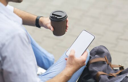 Takeout Coffee And Smartphone With Blank Screen In Hands Of Unrecognizable Man Sitting Outdoors, Over Shoulder Shot, Cropped