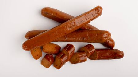 Meat substitute. Meatless smoked sausage whole and sliced on white background