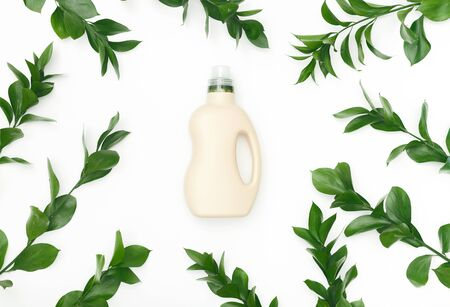 Natural mix for effective laundry washing in bottle on white background surrounded by green plants, eco washing for housekeeping
