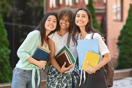 Female Students. Portrait Of Happy Girls University Friends Embracing And Posing Together Outdoors In Campus, Holding Workbooks And Smiling