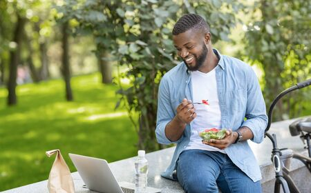 Lunch Fun. Young Black Guy Eating Takeaway Salad Outdoors And Watching Videos On Laptop, Relaxing On Bench In Park