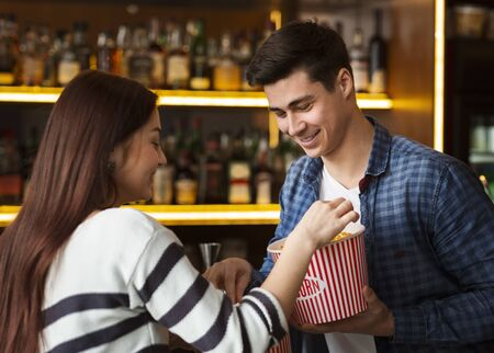 Recreation and leisure. Happy girl with her boyfriend having snacks in cinema lobby