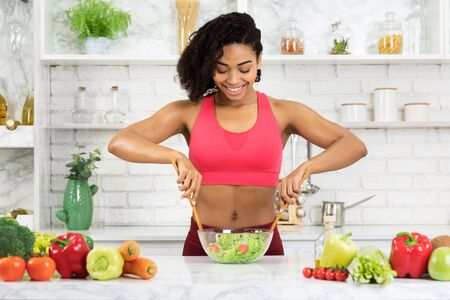 Healthy Eating For Slim Body Concept. Fit black girl cooking vegetable salad in modern kitchen, copyspace