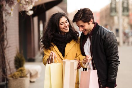 Look What I Bought. Cute girl showing her boyfriend whats inside her paper bags after shopping, copyspace Stok Fotoğraf