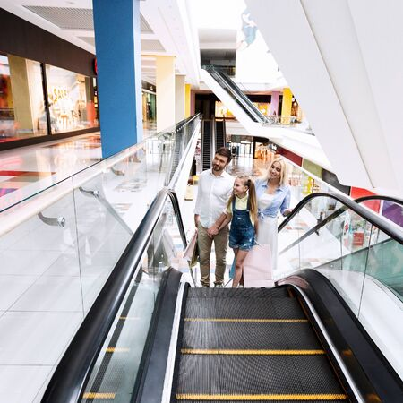 Family On Shopping Moving Up Standing On Escalator Stairs In Hypermarket Holding Shopper Bags. Empty Space