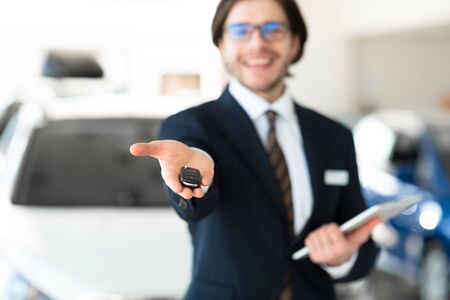 Salesperson Showing Auto Key To Camera Standing In Automobile Rental Office. Copyspace, Selective Focus