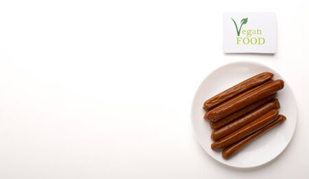 Organic protein sources. Meatless sausages on plate with logo vegan food, free space