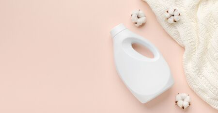 Liquid detergent bottle and white wool sweater. Fabric softener. Regular washing. Laundry concept. Empty place for text or logo on pastel pink background, panorama 免版税图像