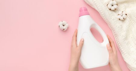 Advertisement of washing detergent with softener, woman holding bottle over pink background with cotton flowers, panorama, copy space