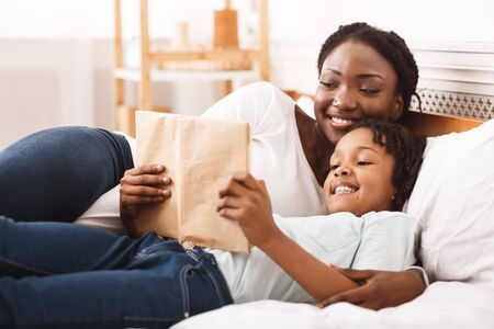 Bedtime Story. Happy black mom and her child reading book together, lying in bed at home, copy space