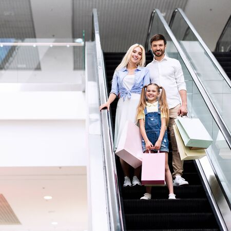 Shopping. Young Parents And Daughter Holding Shopper Bags Standing On Escalator Stairs Moving Down In Mall Center. Free Space