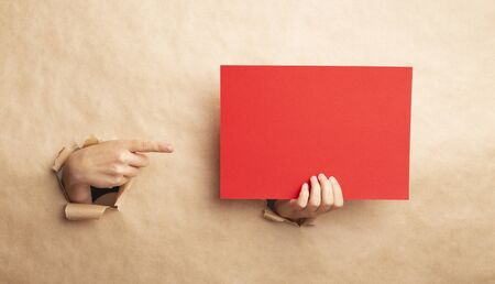 Young lady pointing at empty red sheet through gap in kraft paper, blank space for design