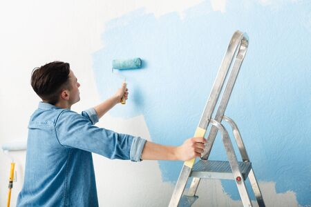Young man leans on stepladder and paints wall with roller, free space 写真素材