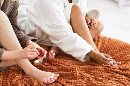 Cropped of two multiracial women making pedicure, polishing nails, sitting on bed in bathrobes