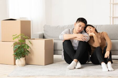 Foreclosure Concept. Sad asian family sitting on the floor with cardboard boxes, moving because of epidemic Reklamní fotografie