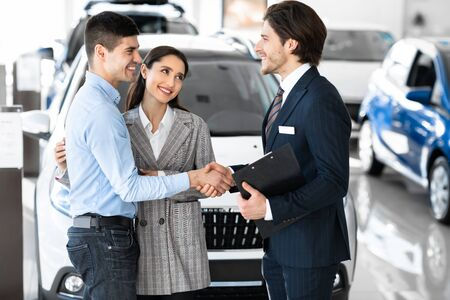 Pleasure Working With You. Beautiful couple embracing after buying new car, shaking hands with salesman Archivio Fotografico