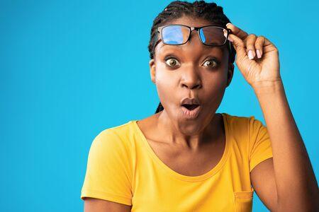 Unbelievable. Shocked African Woman Looking At Camera Rising Eyeglasses In Shock Posing Over Blue Background. Studio Shot, Free Space