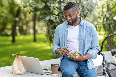 Smiling Black Guy Eating Vegetable Salad And Drinking Coffee While Relaxing With Laptop In Park During Break At Work