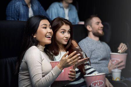 Weekend getaway. Smiling young girls enjoying their movie night in cinema