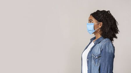 Profife portrait of scared african american woman wearing protective medical mask and looking aside at copy space on light studio background, panorama