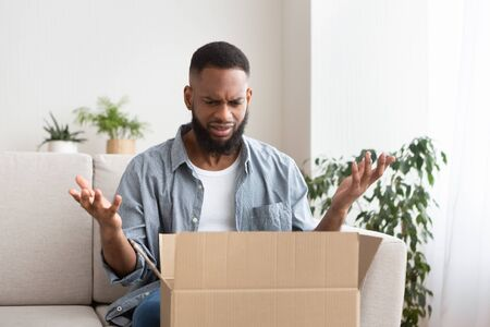 Shocked african american man spreads his hands, having problem with bad shopping order
