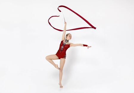 Sports competition. Beautiful gymnast woman in red leotard doing exercises with ribbon on white background
