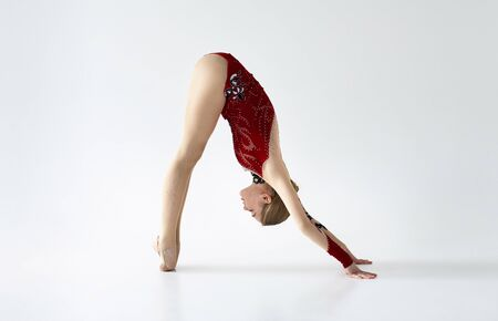 Professional gymnast in red sports suit stretching before performance on white background