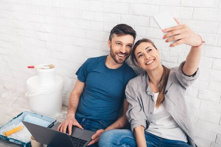 Family, moving, relations, first home concept. Young couple Sitting near the wall and making selfie over white bricks wall