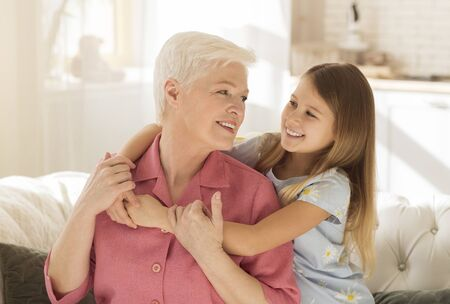 Happy family moments. Cute girl happily embracing her granny at home