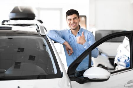 Great Car. Cheerful Guy Standing Near Auto Gesturing Thumbs Up Buying Vehicle In Dealership Center. Free Space